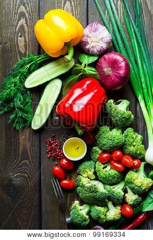 Composition with variety of fresh organic vegetables on wooden background