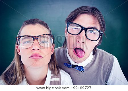 Funny geeky hipsters grimacing against green chalkboard