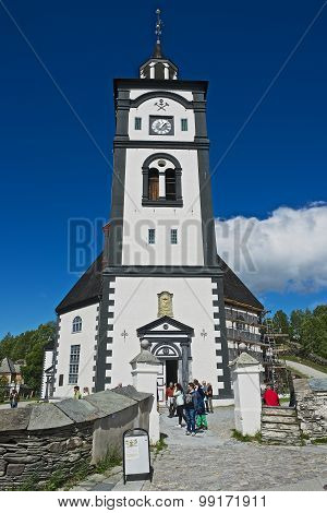 Tourists walk in front of the Roros church and bell tower in Roros, Norway.