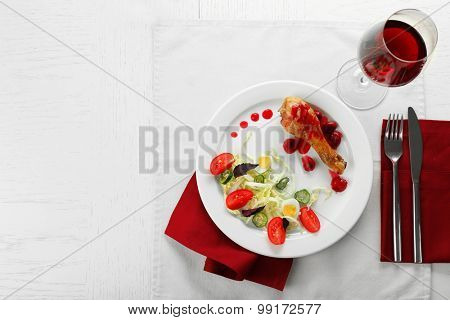 Tasty dinner served with wine on table close up