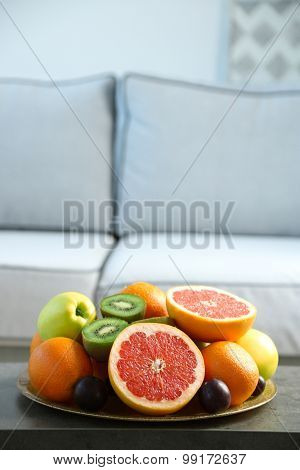 Fresh fruits on table in living room, close up