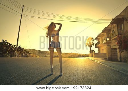 Beautiful woman walking in a solitary road at sunset