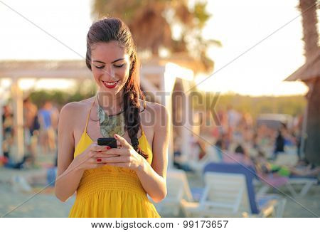 Woman wearing a yellow dress, using her smartphone