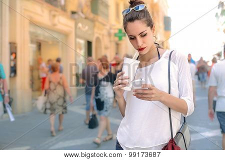 Young woman with smoothie and smartphone
