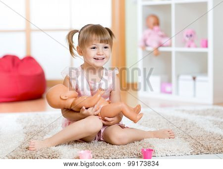 Smiling little girl playing with a doll at home