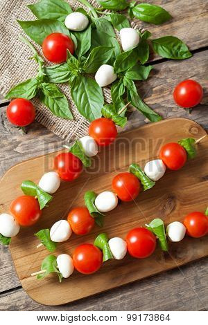Delicious healthy antipasti snack caprese, skewers with mozzarella basil and tomatoes. Healthy organ