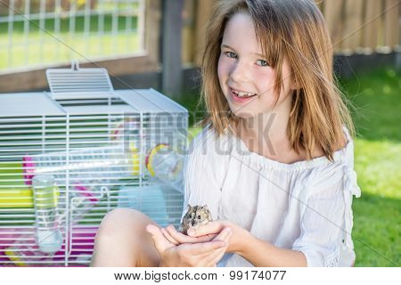 Happy little girl sitting in the backyard with a small hamster in hands
