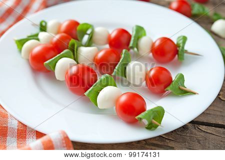 Caprese traditional mediterranean salad skewers with mozzarella basil and tomatoes on white dish. Vi