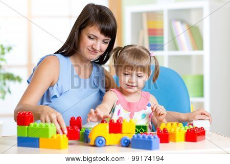Cute little girl playing block with mother at home