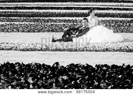 Bride And Groom Sitting On Lawn With Flowers Bw