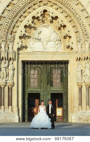 Bride And Groom Standing In Front Of Cathedral