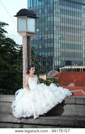 Bride Sitting Next To Street Lamp