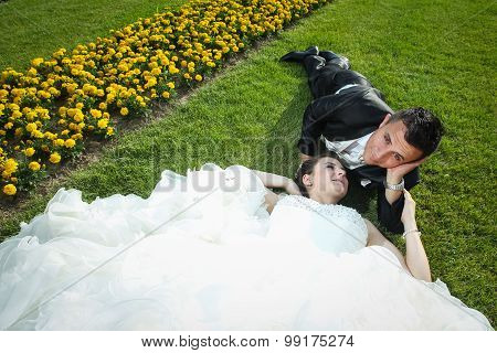 Newlyweds Lying Down On Lawn With Flowers