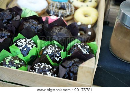 Different sweet cakes in crate close up