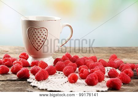 Fresh raspberries with cup of tea on wooden table with napkin on light blurred background