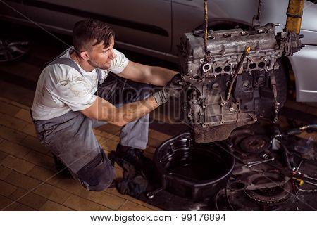 Service Station Worker Repairing Motor