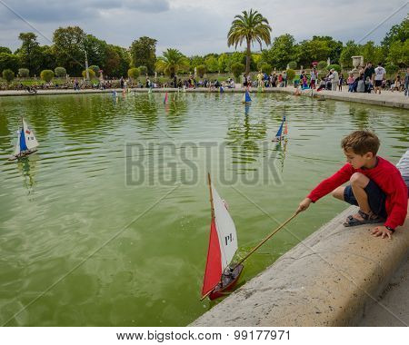 Boy plays with a sailboat in the pond at the Luxembourg Gardens
