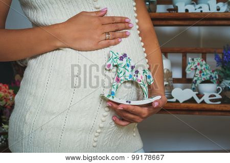 Pregnant Woman Holding Horse-toy Near Her Belly