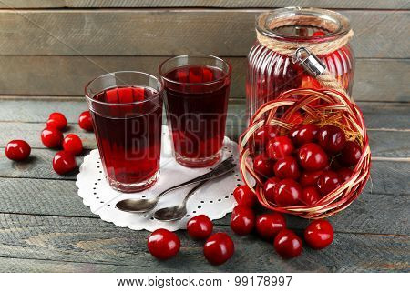 Glasses of sweet homemade cherry compote on table on wooden background