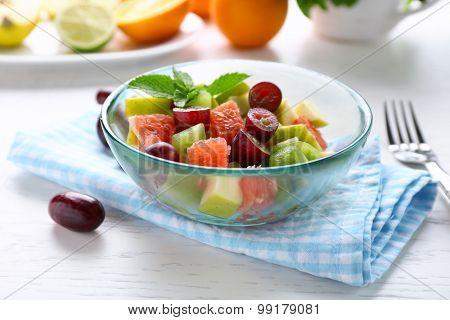 Fruit salad in glass bowl, on light wooden background