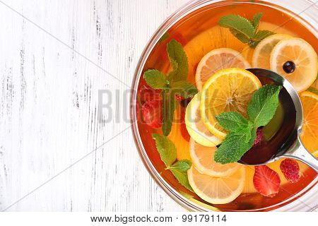 Fruity punch in glass bowl on wooden table, top view