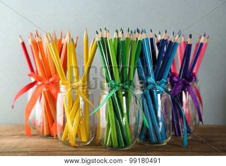 Bright pencils in glass jars on wooden table, on grey background