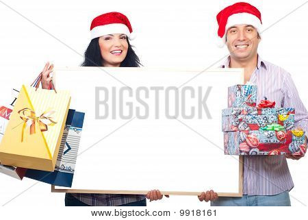 Happy Couple Holding Banner And Xmas Gifts