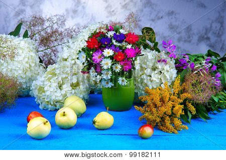 Mixed flowers and fruits on a wooden table