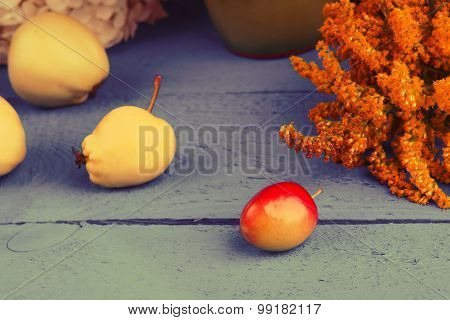 Plum, apples and flowers on a table