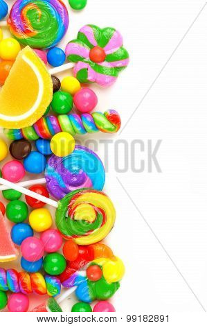 Side border of colorful candies over white