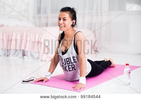 Girl doing warming up exercise for spine, backbend, arching stretching her back  working out at home