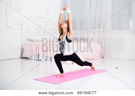 Beautiful athletic sporty woman in the gym doing exercises on mat raising her hands