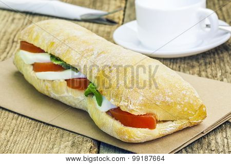 Filled baguette with mozzarella cheese on table