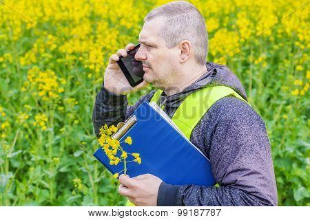 Farmer with folder and cell phone near yellow rape field