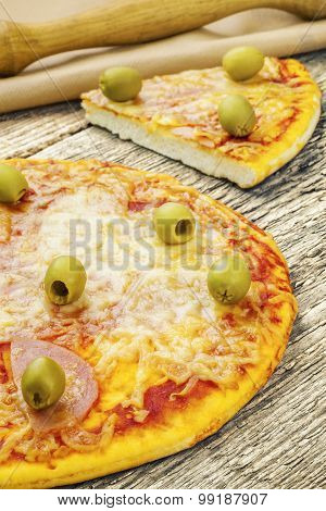 Pizza with ham and green olives