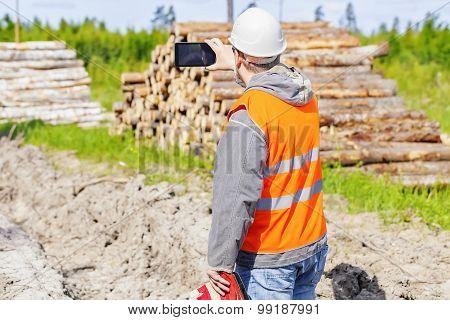 Forest engineer with tablet PC in forest in summer