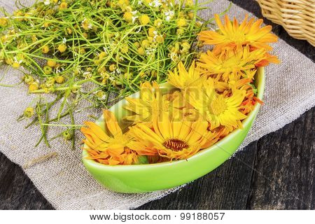 Marigold flowers in bowl with dry chamomile on the background