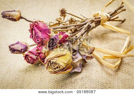 Dried roses on rustic jute fabric