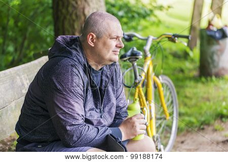 Man with bottle of water on bench near bicycle