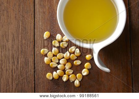 maize corn and cup of corn oil on wooden table