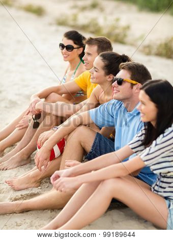 summer holidays, sport, leisure and people concept - group of happy friends sitting on beach with ball
