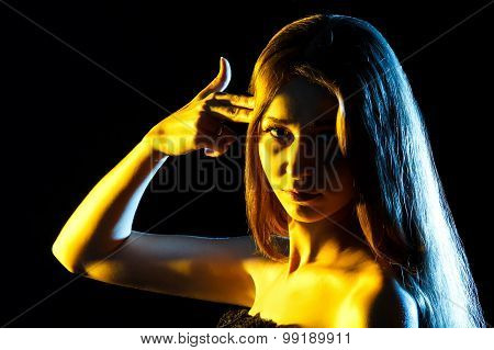 Beautiful Young Woman In Yellow Lights Pointing Fingers To The Head Like Shooting A Gun
