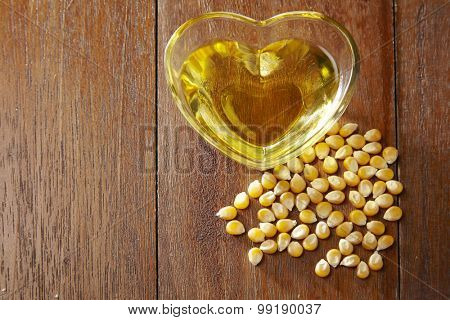 maize corn and glass of heart shape container filled up with corn oil