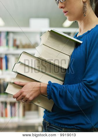 Woman Holding Pile Of Books In Library