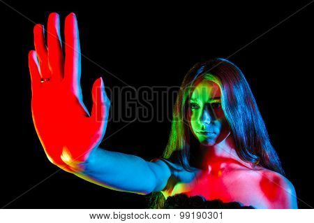 Beautiful Young Woman In Red, Green And Blue Lights Showing The Stop Sign