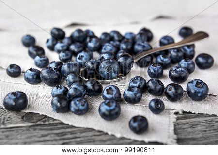 Blueberries Lie On A Homespun Tablecloth And In Metal Spoon. Rustic Cozy Background