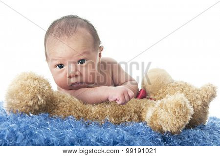 Close-up of an adorable newborn attempting to climb over his fluffy tan Teddy bear.  On a white background.