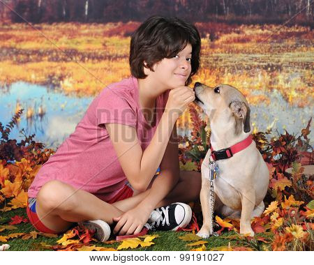 An attractive Hispanic girl  posing with her mutt as the dog accepts her reward - outside on a warm autumn day.