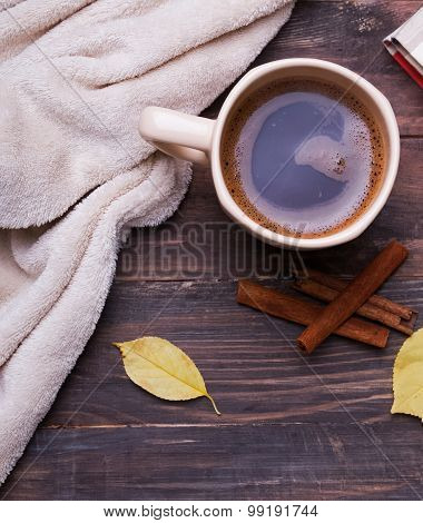 Cup Of Coffee And Cozy Blaket On Wooden Backrgound