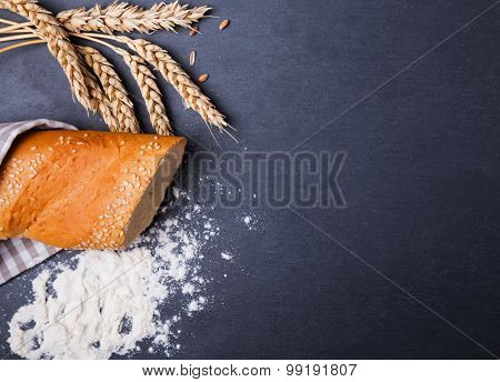 Bread, Wheat Ears And Flour On The Black Background